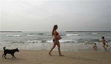 A woman and her dog walk along the beach in this file photo. REUTERS/Gil Cohen Magen