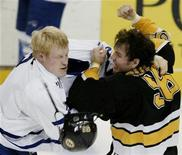 <p>Toronto Maple Leafs' Wade Belak (L) knocks the helmet off Boston Bruins' Doug Doull as they fight in first period NHL action in Boston, Massachusetts, January 1, 2004. REUTERS/Brian Snyder</p>