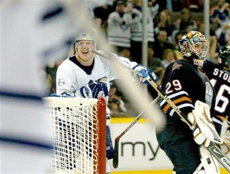 Toronto Maple Leafs forward Wade Belak (L) watches his teammates celebrate their third period goal against the Edmonton Oilers during NHL action in Edmonton January 7, 2006. Oilers goaltender Ty Conklin (R) watches Leafs Chad Kilger (not in picture) and Clarke Wilm (jersey seen at L) celebrate. The goal, scored by Kilger, proved to be the winner as Toronto defeated Edmonton 3-2. REUTERS/Dan Riedlhuber