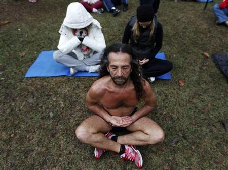 People perform yoga during a gathering calling for world peace, at Ibirapuera Park in Sao Paulo August 21, 2011. REUTERS/Nacho Doce