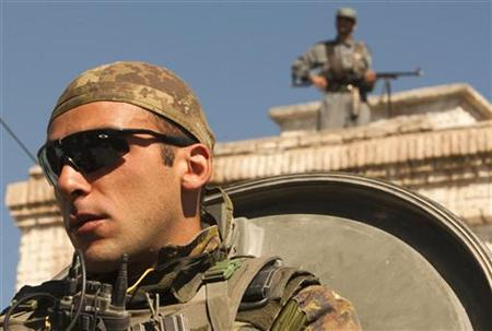 An Italian soldier of NATO's International Security Assistance Force (ISAF) stands guard as an Afghan policeman stands on a roof, in Herat's prison, western Afghanistan September 14, 2010. REUTERS/Raheb Homavandi