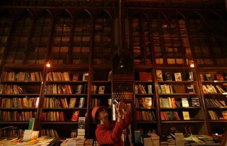 A woman takes a picture in a bookstore in this file photo. REUTERS/Rafael Marchante