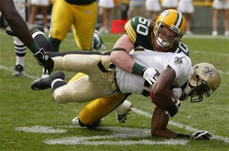New Orleans wide receiver Marques Colston is tackled by Green Bay Packers first round draft pick linebacker A.J. Hawk (50) on a five yard pass in the fourth quarter of their NFL football game at Lambeau Field, Green Bay, Wisconsin September 17, 2006. REUTERS/Allen Fredrickson