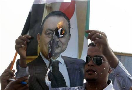 An anti-Mubarak demonstrator burns a picture of former Egyptian president Hosni Murbarak in front of the police academy where his trial is taking place in Cairo September 5, 2011. REUTERS/Amr Abdallah Dalsh