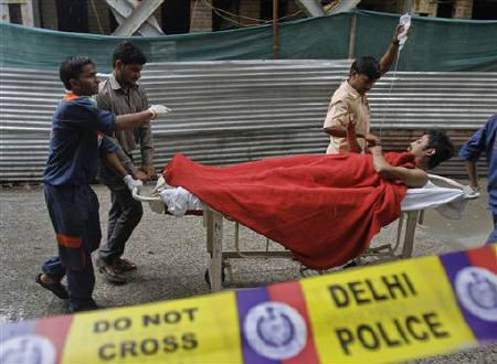 Men carry a man, who was injured by a bomb blast outside the High Court in New Delhi, on a stretcher to a hospital for treatment September 7, 2011. REUTERS/Vijay Mathur