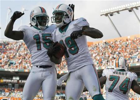 Miami Dolphins Davone Bess (L) celebrates with teammate Brandon Marshall after Marshall scored a touchdown against the Buffalo Bills during the fourth quarter of their NFL game in Miami, Florida December 19, 2010. The National Football League and ESPN have agreed to a deal that will keep ''Monday Night Football'' on the cable sports network through 2021, extending the current contract by eight years, the two sides said on Thursday. REUTERS/Hans Deryk