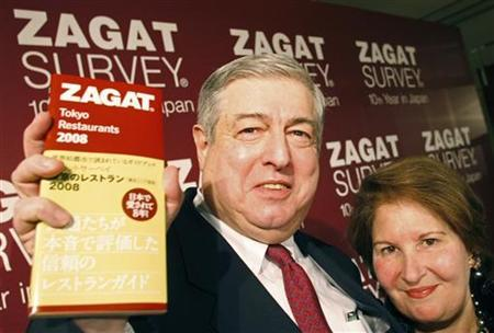 Zagat Survey co-founders Tim (L) and Nina Zagat pose with the latest version of their guide to Tokyo restaurants at a news conference in Tokyo December 19, 2007. REUTERS/Kim Kyung-Hoon