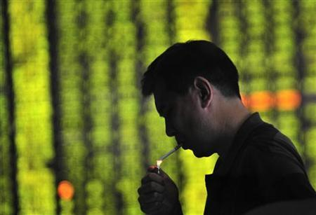 A man lights up a cigarette in front of an electronic screen displaying stock information at a brokerage house in Shenyang, Liaoning province August 2, 2011. REUTERS/Stringer