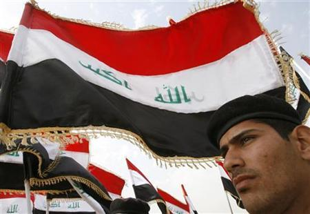 One of the 897 trainees of the national police force march under the new Iraqi flag at their graduation ceremony in Baghdad February 11, 2008. REUTERS/Thaier al-Sudani