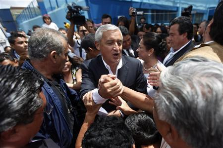 Guatemala's Patriot Party (PP) presidential candidate Otto Perez Molina shakes hands with his supporters after casting his ballot in Guatemala City September 11, 2011. REUTERS/Edgard Garrido