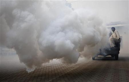 A man fumigates against mosquitoes through the streets of Lahore March 28, 2011. REUTERS/Mohsin Raza
