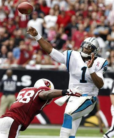 Carolina Panthers quarterback Cam Newton (R) throws down field as he is tackled by Carolina Panthers linebacker Thomas Davis in the third quarter of their NFL football game in Glendale, Arizona September 11, 2011. REUTERS/Rick Scuteri