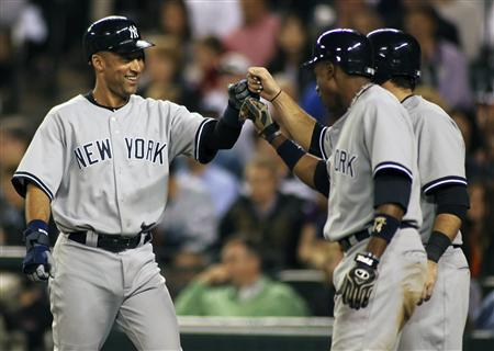 New York Yankees' Derek Jeter (L) celebrates with teammates Curtis Granderson (R) and Austin Romine (partically obscured) all of the scoring during the seventh inning off a double hit by Robinson Cano against the Seattle Mariners in their MLB American League baseball game at Safeco Field in Seattle September 12, 2011. REUTERS/Anthony Bolante
