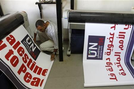 A Palestinian worker inspects a banner as it prints in the West Bank city of Ramallah September 12, 2011. REUTERS/Mohamad Torokman