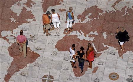People walk over a world map engraved in marble in Lisbon, September 14, 2011. REUTERS/Jose Manuel Ribeiro
