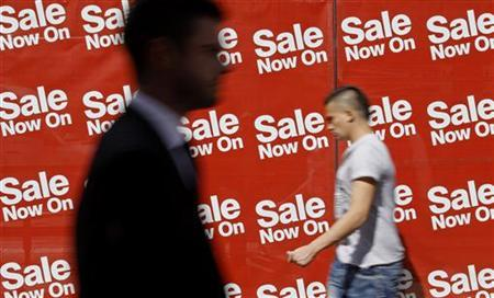 Pedestrians walk past sale signs in the windows of a shop on Oxford Street in London August 25, 2011. REUTERS/Luke MacGregor