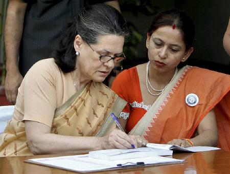 Sonia Gandhi (L), Congress party chief, is assisted by a census official to record details of herself and her family members for census, in New Delhi April 10, 2010. REUTERS/Stringer/Files