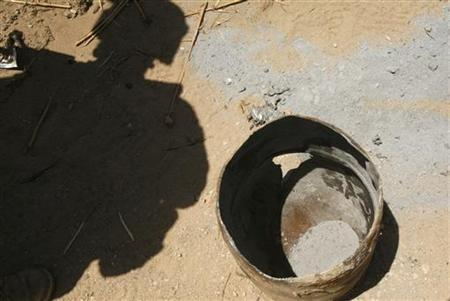 A U.S. Marine from 3rd Battalion, 6th Marines looks at a barrel which was used for an IED and its powder after it exploded, during a patrol in Marjah district, Helmand province, May 18, 2010. REUTERS/Asmaa Waguih