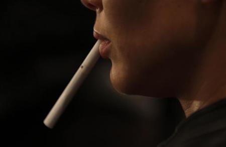 A model holds an unlit cigarette in her mouth backstage before the Zang Toi Spring 2011 collection during New York Fashion Week September 15, 2010. REUTERS/Eric Thayer