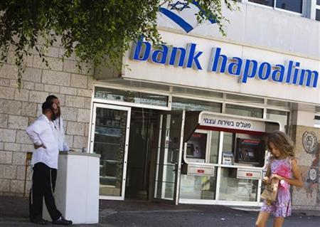 People stand beside a branch of Bank Hapoalim, Israel's second largest bank which is controlled by Shari Arison's Arison group, in the southern city of Ashkelon July 27, 2011. REUTERS/Amir Cohen