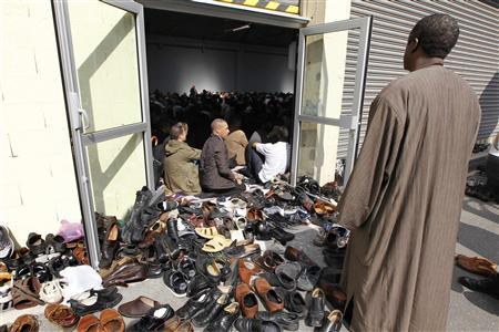 Shoes are seen outside a makeshift prayer site as Muslims celebrate Friday prayers at a former fire brigade in Paris September 16, 2011. REUTERS/Charles Platiau