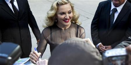 Director Madonna pauses to sign autographs at the premiere of her film ''W.E.'' at the 36th Toronto International Film Festival (TIFF) September 12, 2011. REUTERS/Fred Thornhill