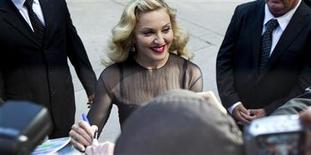 "<p>Director Madonna pauses to sign autographs at the premiere of her film ""W.E."" at the 36th Toronto International Film Festival (TIFF) September 12, 2011. REUTERS/Fred Thornhill</p>"