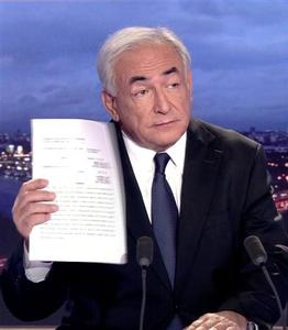 Dominique Strauss-Kahn, former International Monetary Fund chief (IMF), in this still image taken from TF1 television footage, holds a document as he appears on their prime time news programme in their studios in Boulogne-Billancourt, near Paris, September 18, 2011. REUTERS/TF1/Handout