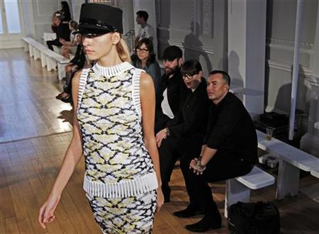 Designer Julien MacDonald (R) watches a catwalk rehearsal ahead of his 2012 Spring/Summer collection during London Fashion Week September 17, 2011. REUTERS/Luke MacGregor