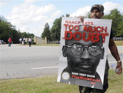 Reverend Archie (last name not given) holds a sign protesting the execution of convicted killer Troy Davis in front of the Georgia Diagnostic and Classification prison, where Davis is set to be executed by lethal injection, in Jackson, Georgia September 21, 2011. REUTERS/Tami Chappell