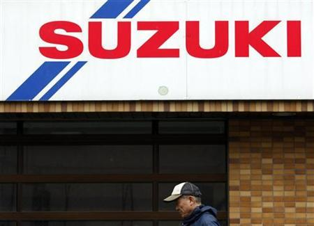 A man walks pasta Suzuki Motor car dealer shop in Tokyo December 9, 2009. REUTERS/Issei Kato