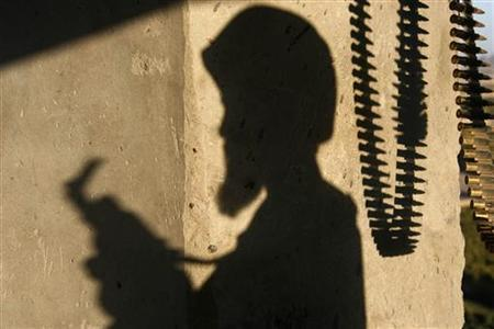 The shadow of an Afghan National Army soldier and bullets are cast on the wall of a lookout tower in Kandahar province, southern Afghanistan, October 14, 2007. REUTERS/Finbarr O'Reilly