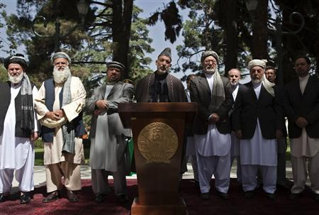 Afghan President Hamid Karzai (C), standing amongst other high ranking government officials, speaks about the assassination of Burhanuddin Rabbani, former Afghan president and head of the government's peace council, at the presidential palace in Kabul September 22, 2011. Rabbani was killed by a suicide attacker in his house on September 20 in Kabul. REUTERS/Ahmad Masood