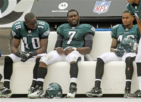 Philadelphia Eagles quarterback Michael Vick (C) sits with a hand injury between Eagles receivers Jeremy Maclin (18) and DeSean Jackson (R) while playing against the New York Giants during the fourth quarter of NFL football action in Philadelphia, Pennsylvania, September 25, 2011. REUTERS/Tim Shaffer