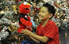 <p>Rio Nguyen, 8, poses for photographers at Hamleys toy store with a Sesame Street Elmo doll in London June 28, 2011. Let's Rock Elmo could be the top toys during the 2011 holiday season, according to an industry guide released on Monday. REUTERS/Paul Hackett</p>