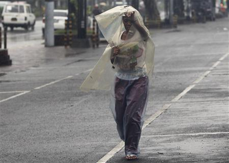 A woman uses a sheet of plastic to protect herself from rain brought by typhoon Nesat, known locally as Pedring, while walking along a main street in Manila, September 26, 2011. REUTERS/Romeo Ranoco
