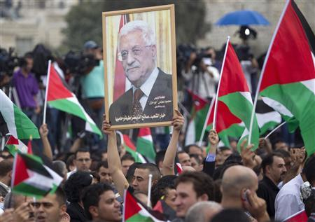 Palestinians hold national flags and a poster of Palestinian President Mahmoud Abbas during a rally in the West Bank city of Ramallah upon Abbas' return from the U.N. General Assembly in the U.S., September 25, 2011.REUTERS/Darren Whiteside