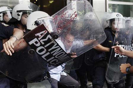 An employee of the Finance Ministry scuffles with riot police at the ministry's entrance in Athens during a protest against the government's austerity measures September 27, 2011. REUTERS/John Kolesidis