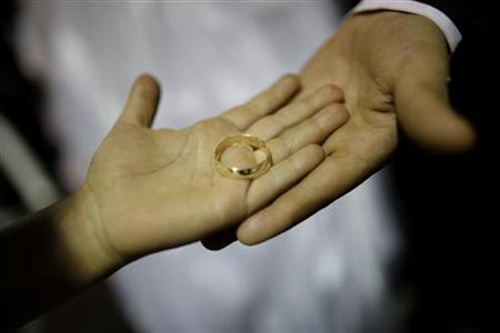 A couple shows a wedding ring as they celebrate in Brasil August 13, 2011. REUTERS/Ueslei Marcelino