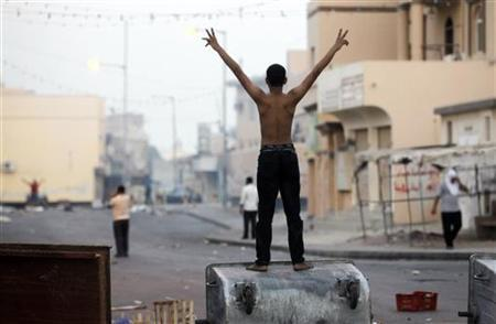 A protester standing on a garbage container shouts anti-government slogans as anti-government protesters try to get back to Manama's Farook Junction, also known as Pearl Square, in Karanna, west of Manama, Bahrain, September 23, 2011. REUTERS/Hamad I Mohammed