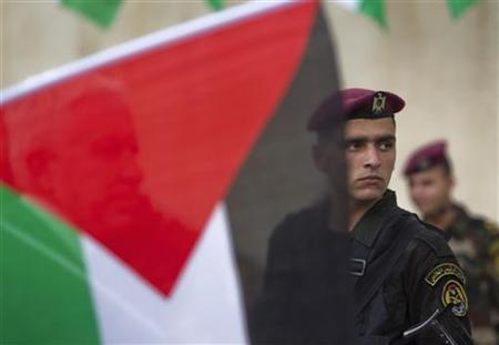 A member of the Palestinian security forces is seen behind a flag during a celebration in the West Bank city of Ramallah upon the return of Palestinian President Mahmoud Abbas from the U.N. General Assembly in the U.S., September 25, 2011. REUTERS/Darren Whiteside