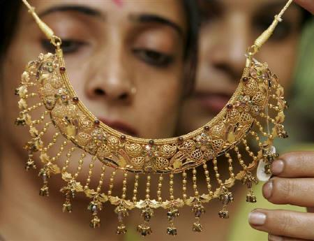 Women admire a gold necklace at a jewellery shop in Chandigarh October 18, 2007. India's commodity exchanges are poised for steady growth over the next few years after annual turnover more than quintupled to $2.5 trillion since futures trading started in 2003, but political hurdles hinder more dramatic development. REUTERS/Ajay Verma/Files