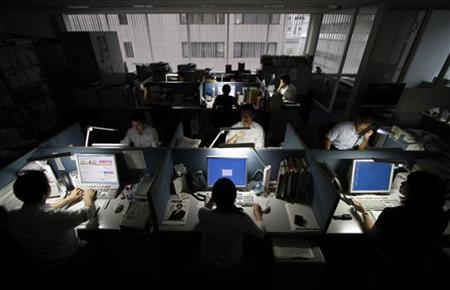 Employees work at a company office in Tokyo June 30, 2011. REUTERS/Toru Hanai