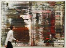 <p>Employee Duncam Holden poses for a photograph with Gerhard Richter's artwork Abstract Painting Abstraktes Bild (CR:726) at the press launch of the new exhibition Gerhard Richter : Panorama at the Tate Modern gallery in London October 4, 2011. REUTERS/Luke MacGregor</p>