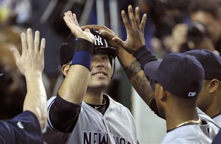 New York Yankees' Jesus Montero (C) is congratulated by teammates after scoring in the eighth inning of Game 4 in their MLB American League Division Series baseball playoffs in Detroit, Michigan, October 4, 2011. REUTERS/Mike Cassese