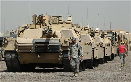 U.S. soldiers walk past tanks at a courtyard at Camp Liberty in Baghdad September 30, 2011. REUTERS/Mohammed Ameen