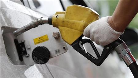 An employee of a gas station fills the tank of a car at a gas station in Seoul June 24, 2011. REUTERS/Truth Leem