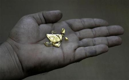 A goldsmith displays a gold nugget at a jewellery workshop in Karachi December 3, 2009. REUTERS/Akhtar Soomro