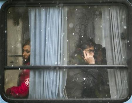 An Iranian man speaks on his mobile phone as he sits in a bus during a snowy day in northern Tehran January 9, 2011. REUTERS/Morteza Nikoubazl