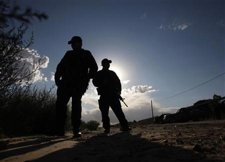 Police officers stand guard at a crime scene where four people were shot dead in Ciudad Juarez September 25, 2011. REUTERS/Jose Luis Gonzalez